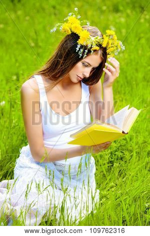 Romantic girl in a wreath of dandelions sitting on the lawn and reading a book. Summer life. Beauty.