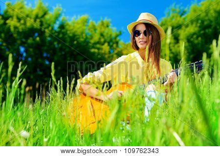 Smiling romantic girl sitting on a grass and playing guitar. Summer day.