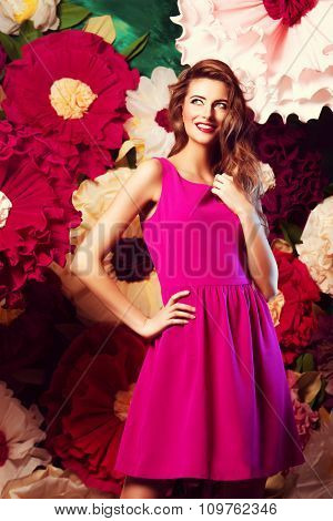 Portrait of a beautiful happy young woman posing on a background of bright large flowers. Beauty, fashion. Summer inspiration.