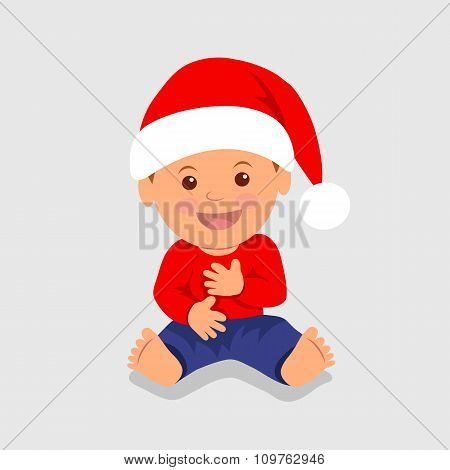 Cute boy sitting in the red Santa hat and laughs.