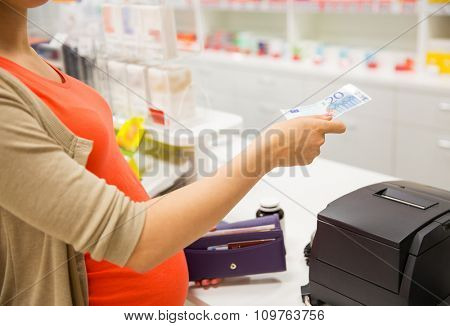 medicine, pharmaceutics, health care and people concept - close up of pregnant woman giving money and buying medication at cash register in drugstore