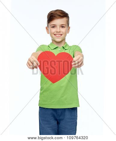 childhood, love, charity, health care and people concept - happy smiling boy in green polo t-shirt holding blank red heart shape