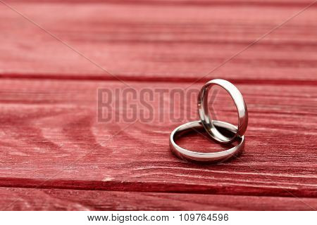 Silver Wedding Rings On A Red Wooden Table