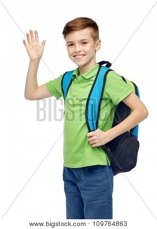 childhood, school, education, greeting gesture and people concept - happy smiling student boy with school bag waving hand