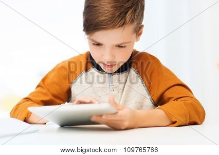 leisure, children, technology and people concept - close up of boy with tablet pc computer at home