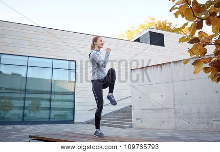 fitness, sport, people and healthy lifestyle concept - happy woman exercising on bench outdoors