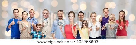 gesture, sale and people concept - group of smiling men, women and kids showing thumbs up and holding shopping bags with money over holidays lights background