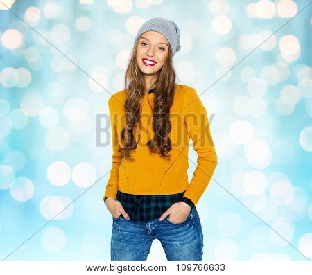 people, style and fashion concept - happy young woman or teen girl in casual clothes and hipster hat over blue holidays lights background