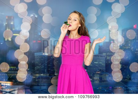 people, holidays and celebration concept - happy young woman or teen girl in pink dress blowing to party horn over night singapore city and lights background