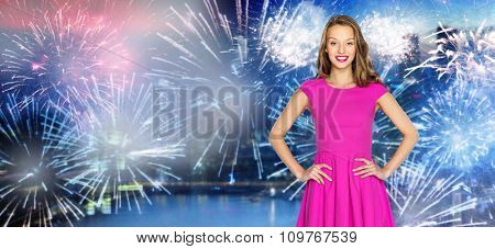 people, holidays, celebration and party concept - happy young woman or teen girl in pink dress over firework at night singapore city background