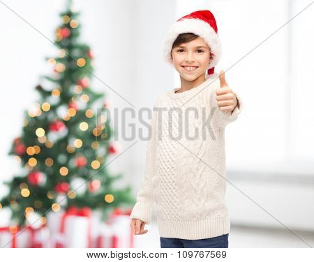 holidays, gesture, christmas, childhood and people concept - smiling happy boy in santa hat showing thumbs up over living room background