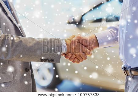 auto business, car sale, deal, gesture and people concept - close up of male handshake in auto show or salon over snow effect