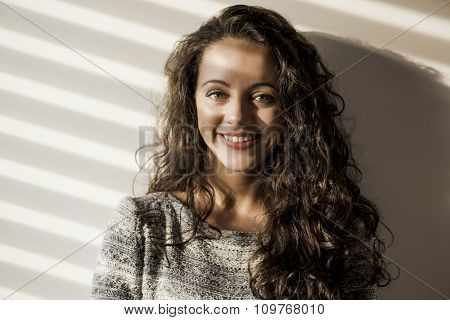 Portrait of a smiling woman on her bedroom