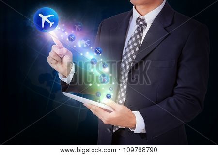Businessman holding tablet with pressing plane sign icon button. internet and networking concept