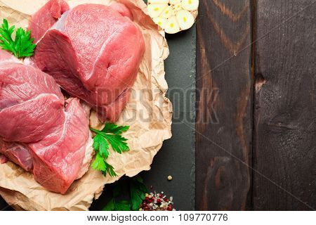 Raw fresh meat with pepper and herbs wrapped in paper over dark stone