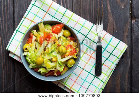 Vegetable salad with tomatoes, cabbage, olives and apple on wooden background