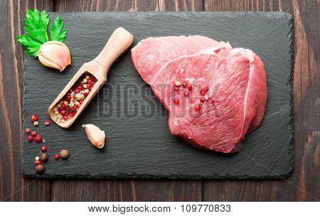 Raw fresh meat with pepper and salt on dark stone cutting board