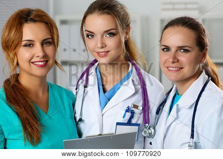 Three Smiling Female Medicine Doctors In Office Looking In Camera Portrait