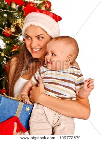 Young mom wearing Santa hat holding  baby boy son with gift box  under Christmas tree on isolated.