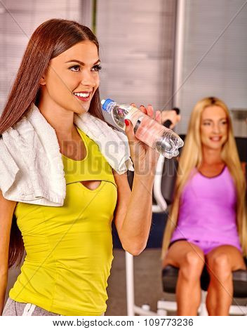 Girls holding bottle and drinking water  in sport gym.