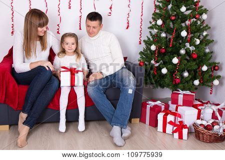 Happy Family Sitting In Decorated Living Room With Christmas Tree