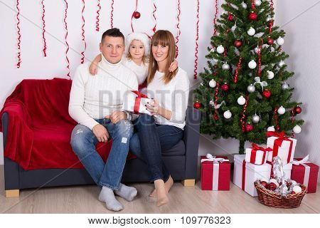 Cheerful Parents With Daughter Sitting Near Christmas Tree At Home