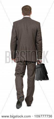 Businessman walking rear view