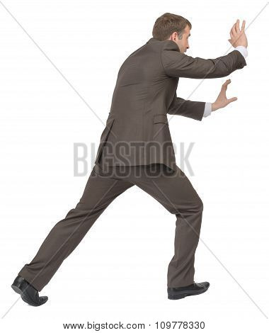 Businessman pushing empty space, side view