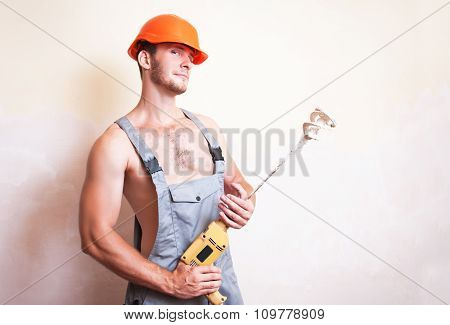 Man In Overalls With A Mixer For Plastering