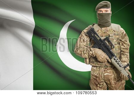 Soldier Holding Machine Gun With Flag On Background Series - Pakistan