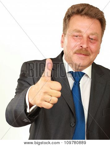 Happy businessman showing his thumb up and smiling while his colleagues standing in the background