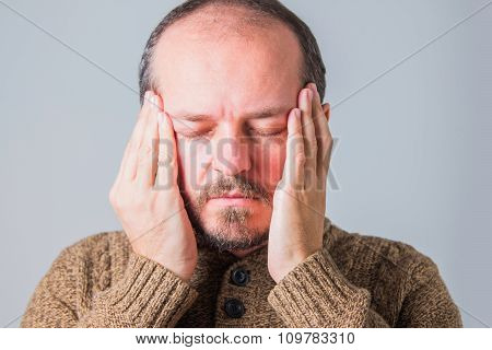 Man with beard in sweater holding both hands on head, having strong headache, indoor, facial express