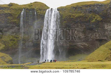 Tourists At  Skogafoss, Iceland On Rainy Day
