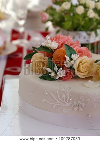 White wedding cake with flowers on the table, close-up