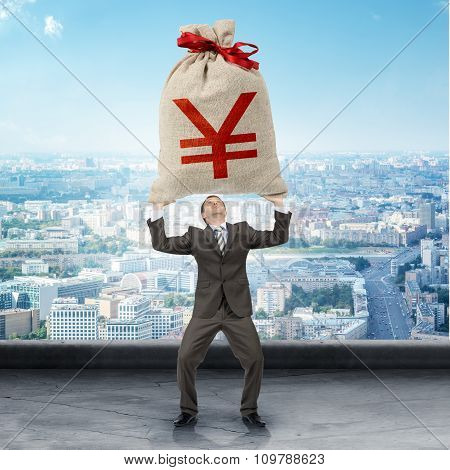 Businessman holding big moneybag with yen sign