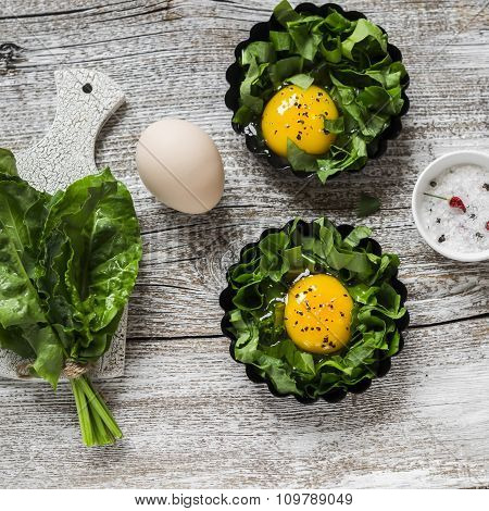 Raw  Ingredients For Making Baked Eggs. Fresh Sorrel And Eggs On A Light Rustic Wooden Background.