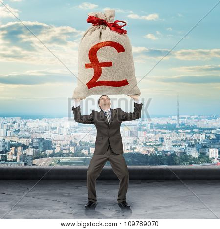 Businessman holding big moneybag with pound sign