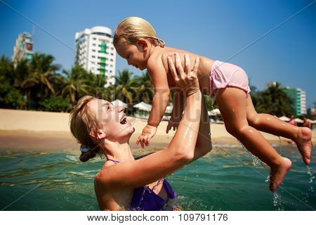 Side-view Mother In Sea Laughs Holds In Arms Small Daughter