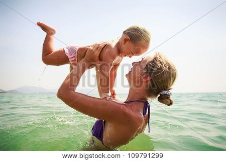 Closeup Side-view Mother Holds Small Daughter Both Smile In Sea