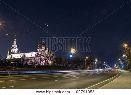 View of the night city with tram tracks and church