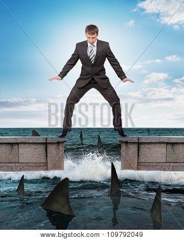 Businessman standing above sharks