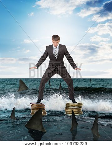 Businessman standing on coins above sharks