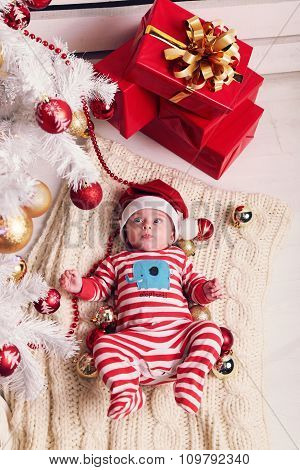 Cute Little Santa Baby Posing Beside Christmas Tree At Cozy Home With New Year Decoration