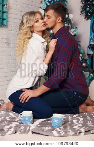 Tender Couple In Elegant Clothes,sitting Beside Christmas Tree At Cozy Home