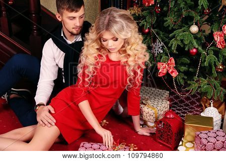 Tender Couple Sitting Beside Christmas Tree ,with Presents And New Year Decoration