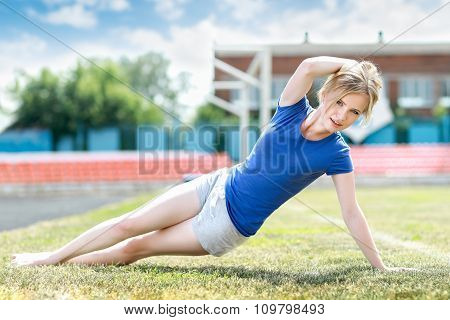 beautiful woman doing core workout at a stadium