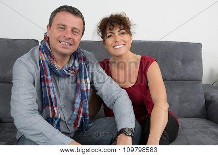 Happy Husband And Wife Hug Looking At Camera