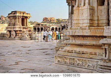 Hampi India - 19 November 2014: People walking in front of stone chariot in courtyard of Vittala Temple in Hampi Karnataka India.