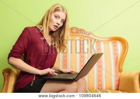 Surprised Woman Sitting On Sofa Using Pc Laptop