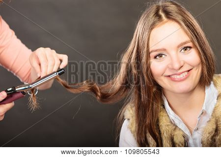 Stylist Curling Hair For Young Woman.